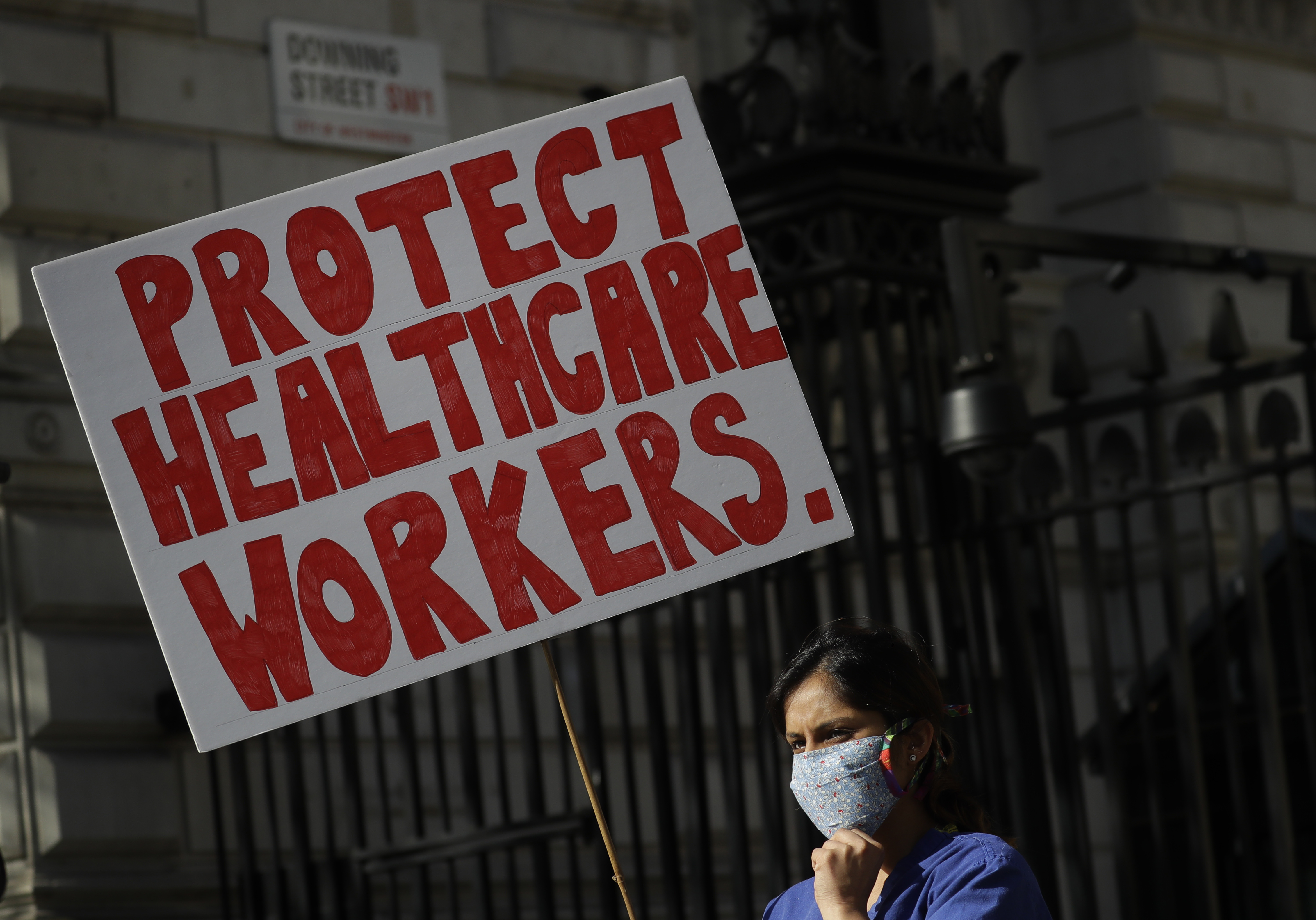 Doctor Meenal Viz holds a banner as she protests outside Downing Street in London, as the country is in lockdown to help curb the spread of the coronavirus