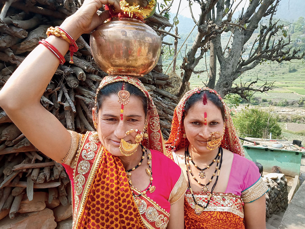 Beautiful women in traditional finery and carrying pitchers making their way to the temple for Chaitra Navratri