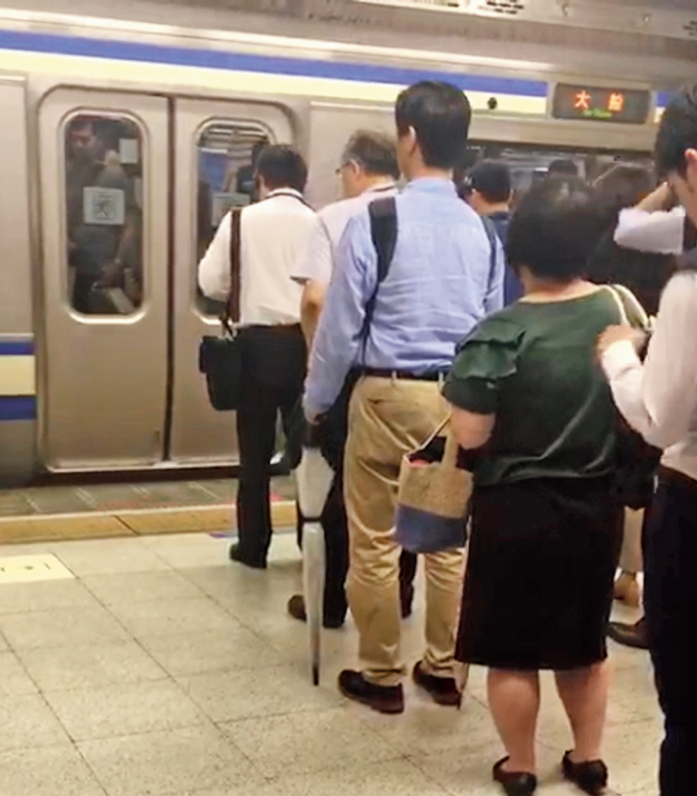 Commuters queue up to board a Metro train in Tokyo