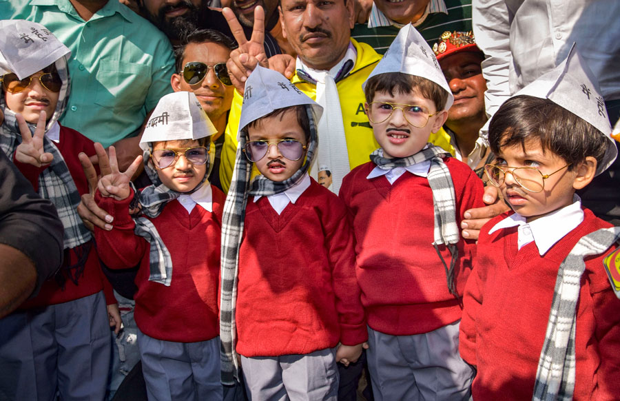 Children dressed as AAP convener Arvind Kejriwal arrive at the Ramlila Maidan for his swearing-in ceremony, in New Delhi