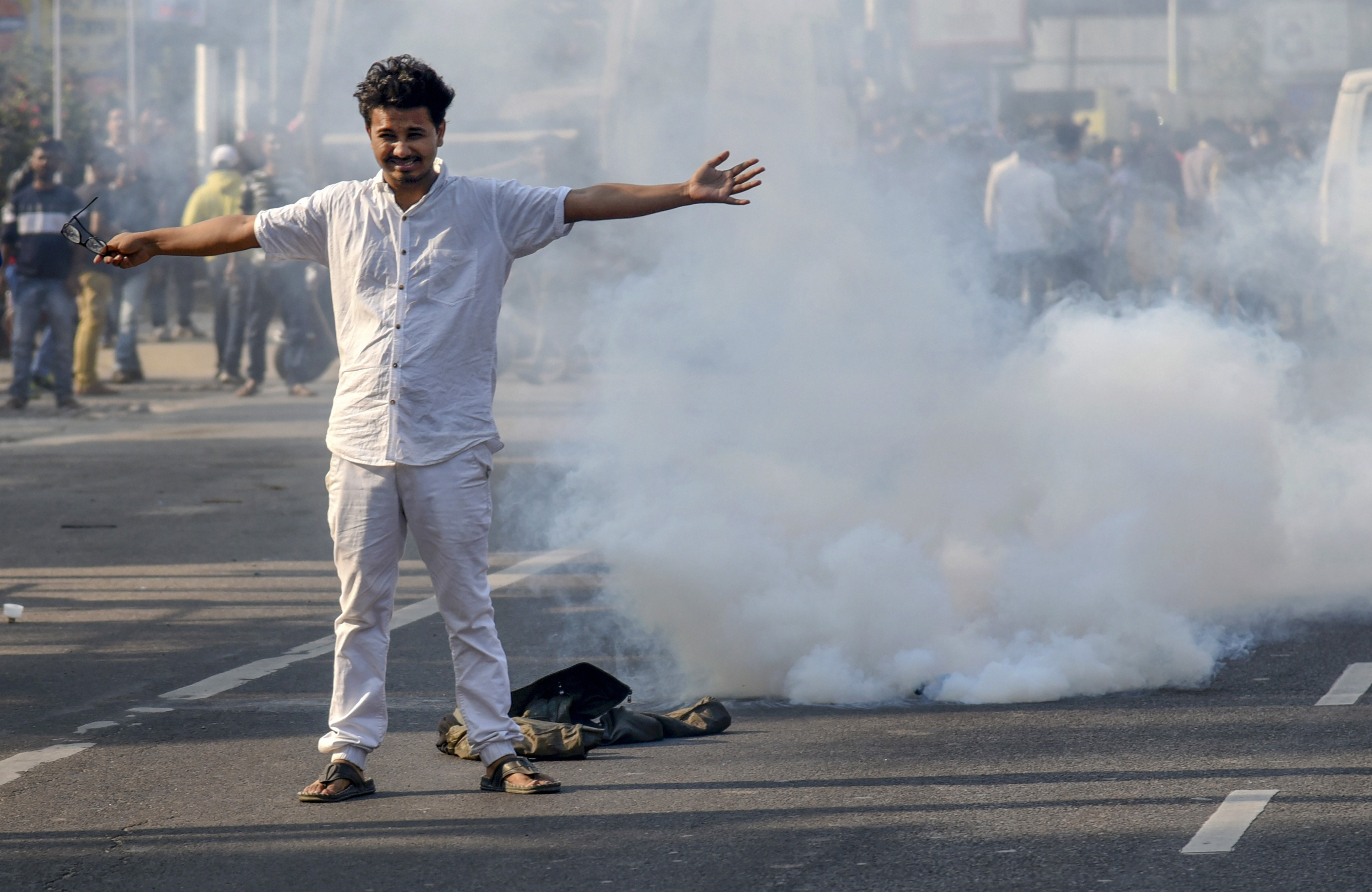 A protester stands in front of a teargas shell during a protest against the Citizenship (Amendment) Bill, in Guwahati, Wednesday, December 11, 2019.