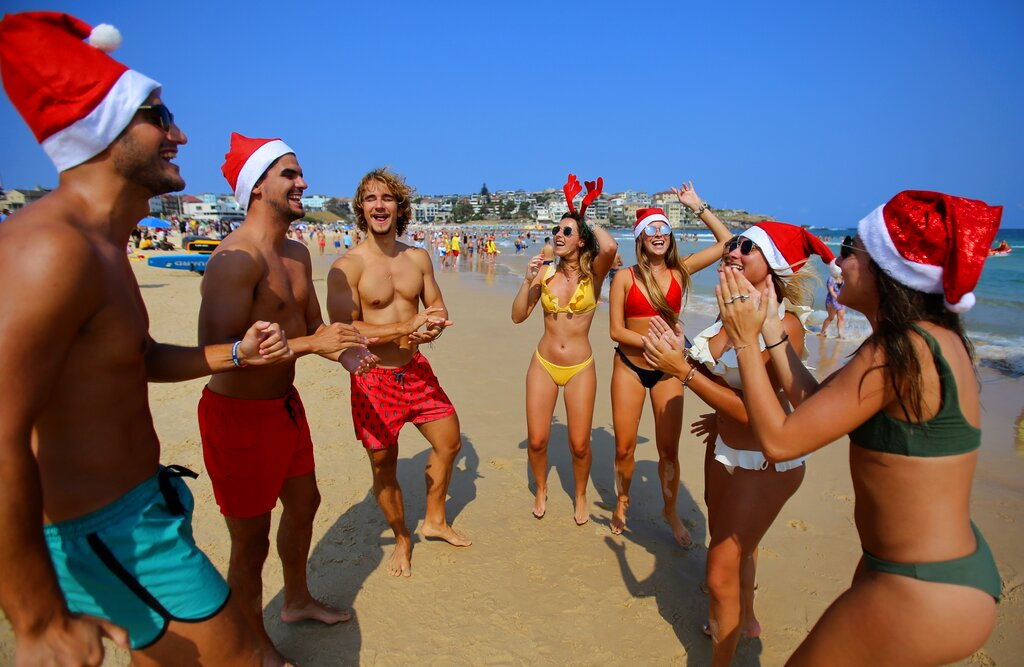 Tourists wearing Christmas outfits dance on the beach on Christmas Day at Bondi Beach in Sydney, Wednesday, Dec. 25, 2019.