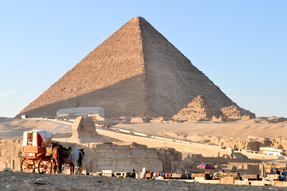 The Egypt pyramids and the stone Sphinx on the Giza platou in endless sands of the Sahara desert.