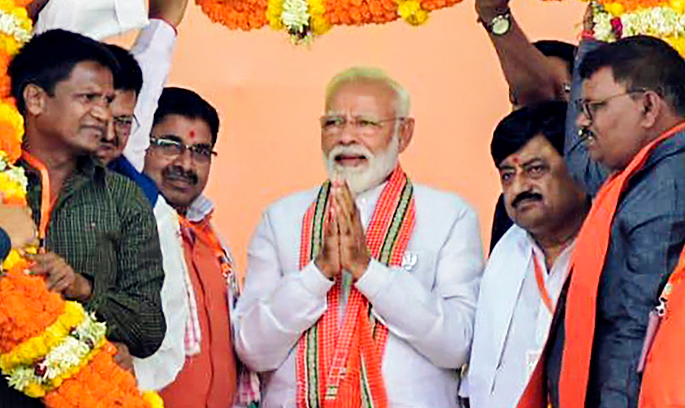 Prime Minister Narendra Modi is garlanded by party workers and leaders during an election rally in Koderma district, Jharkhand, on Monday, April 29, 2019.