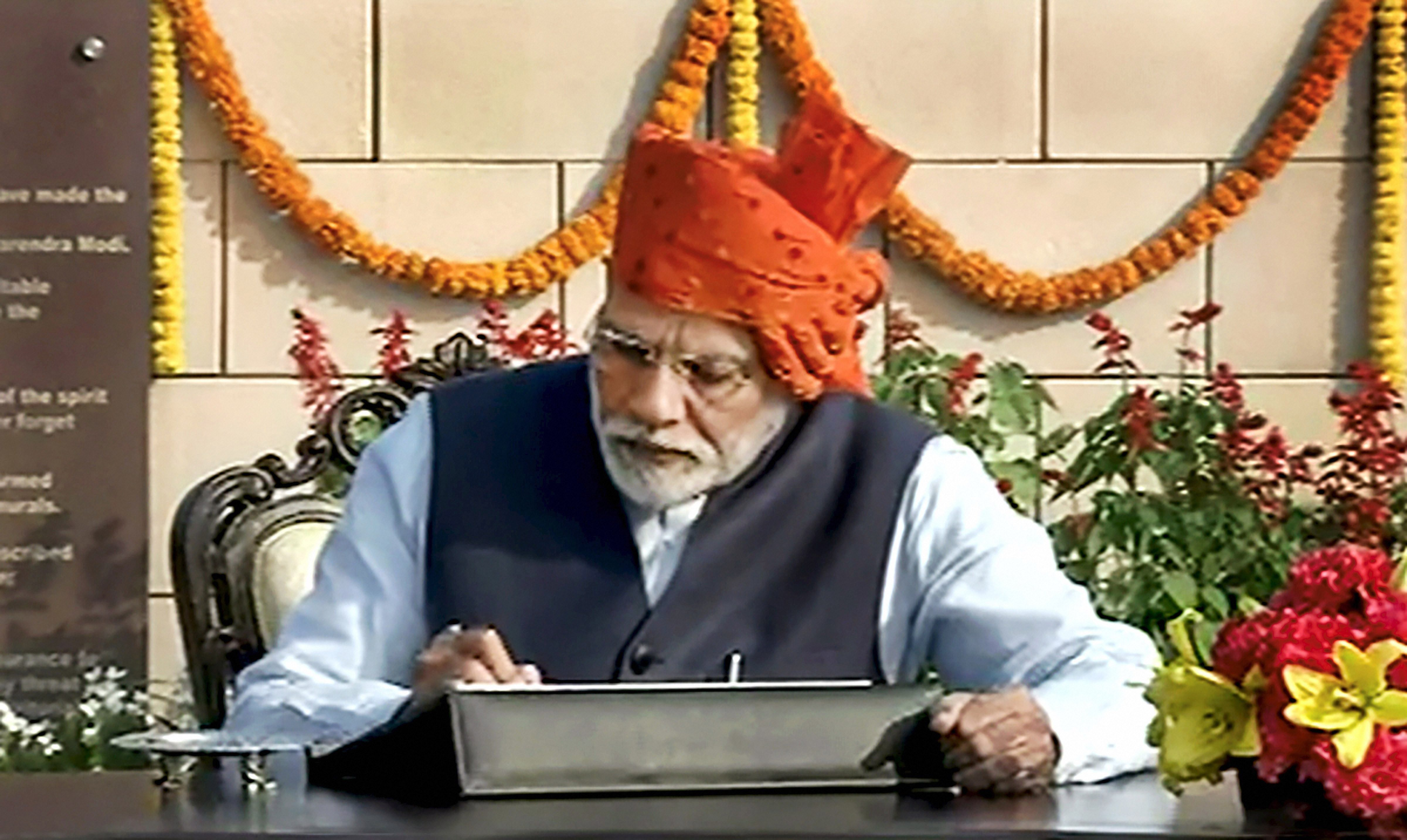 Prime Minister Narendra Modi signs the visitor's book after paying tribute at the National War Memorial near India Gate on the occasion of the 71st Republic Day, in New Delhi, Sunday, January 26, 2019.