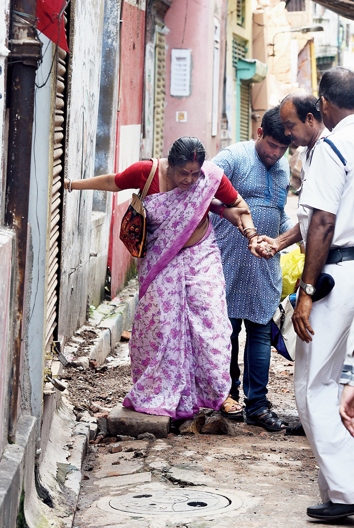 Sandhya Sen, a resident of Durga Pituri Lane, comes out of her house with son Amartya on Wednesday