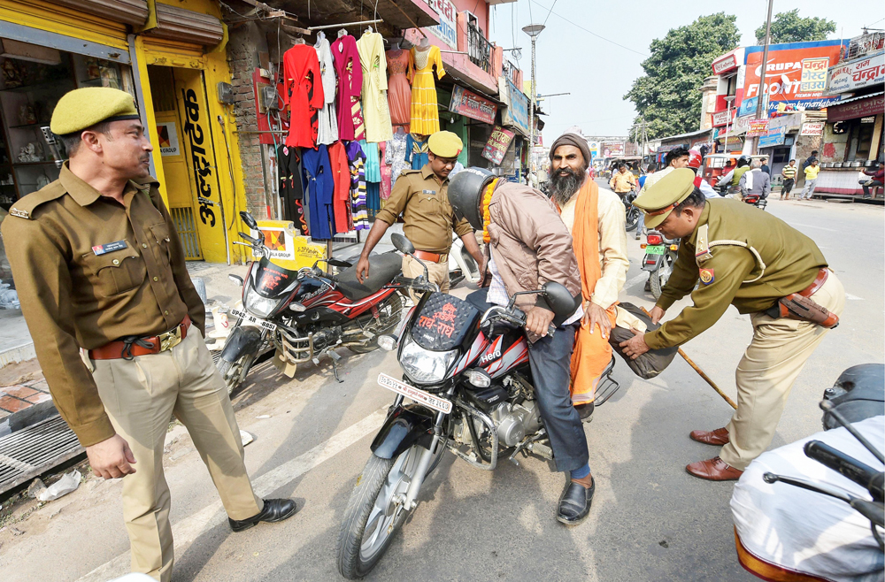 Policemen conduct search of a motorcyclist at a barricade, as part of security measures on the eve of the 27th anniversary of the Babri Masjid demolition, near Hanumangarhi area in Ayodhya, Thursday, December 5, 2019.