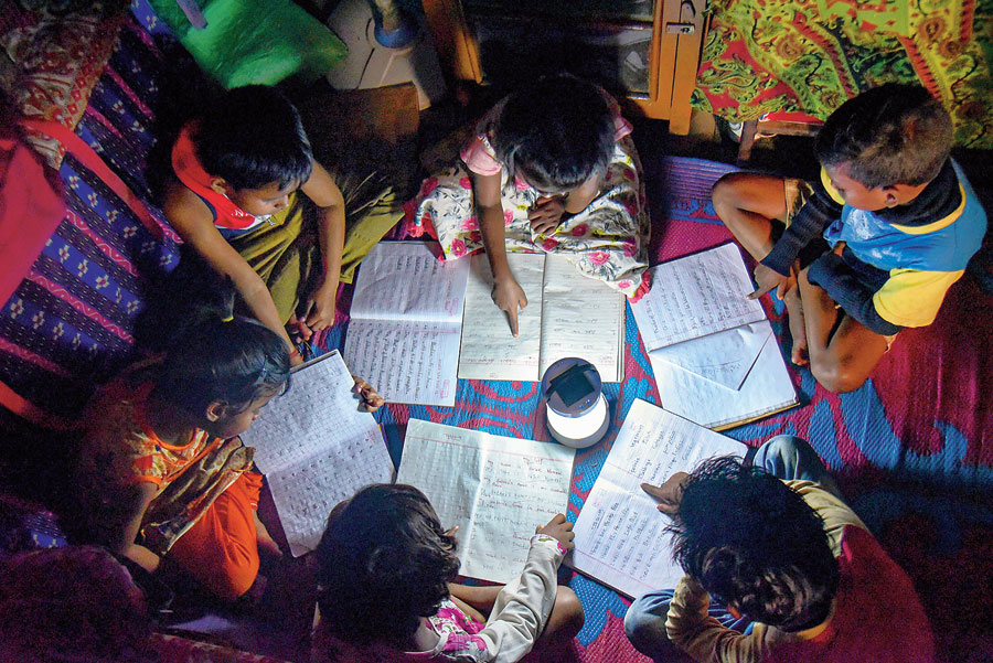 Students use an emergency light to study in Dhanbad on Thursday.