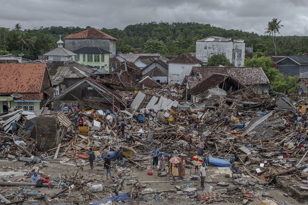People inspect the damage at a tsunami-ravaged village in Sumur, Indonesia on Monday, December 24, 2018
