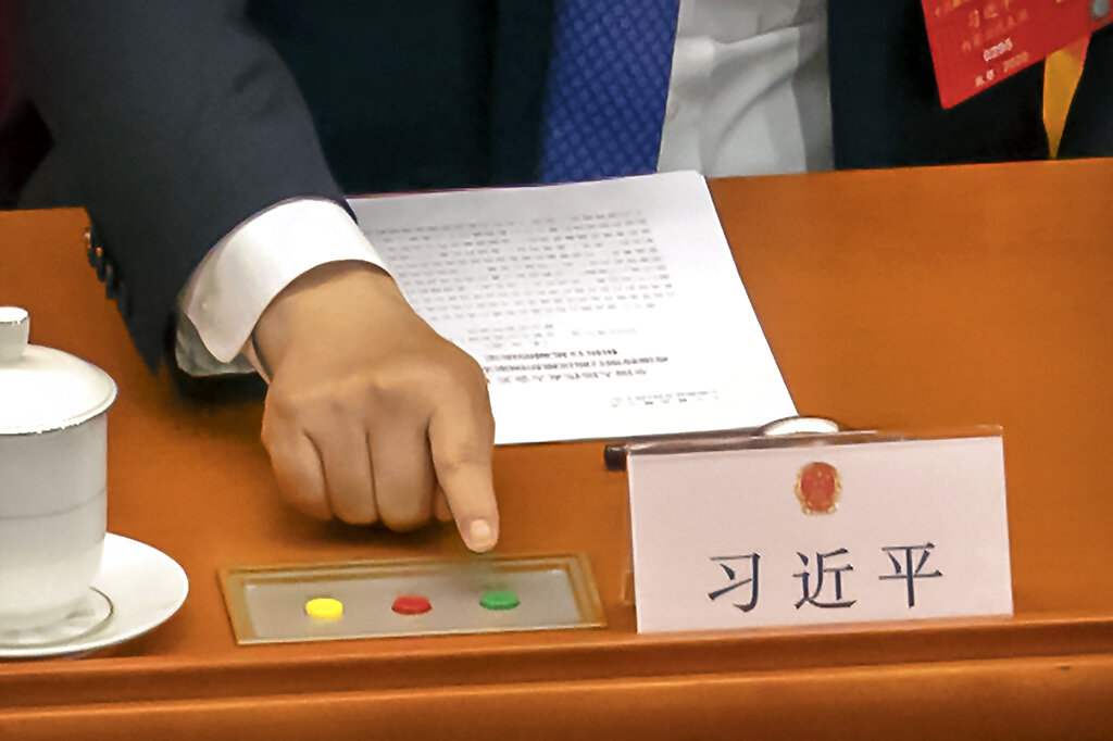 Chinese President Xi Jinping reaches to vote on a piece of national security legislation concerning Hong Kong during the closing session of China's National People's Congress (NPC) in Beijing, Thursday, May 28, 2020.