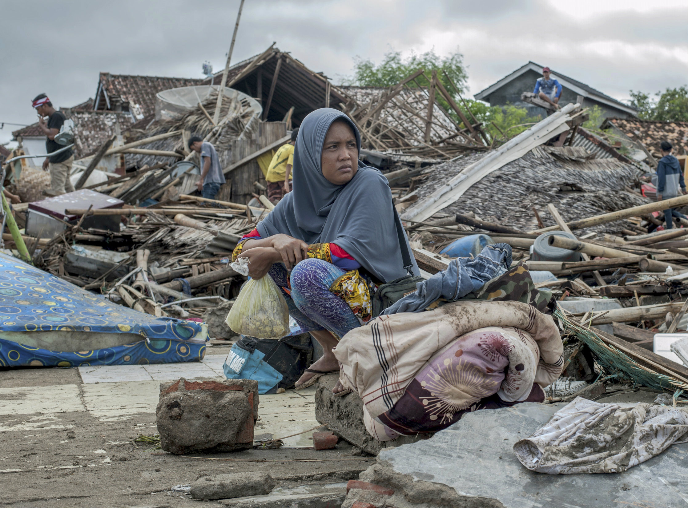 A tsunami survivor sits on debris as she salvages items from her house in Sumur, Indonesia, on Monday.
