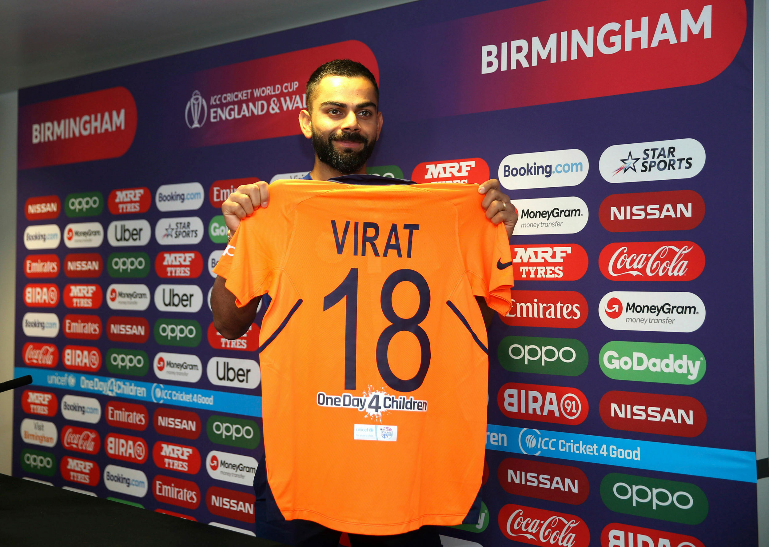 Virat Kohli holds up the new India jersey during a press conference at Edgbaston in Birmingham, on June 29, 2019. India will play in new a new team shirt Sunday to avoid a clash of colours when they play England in the Cricket World Cup.