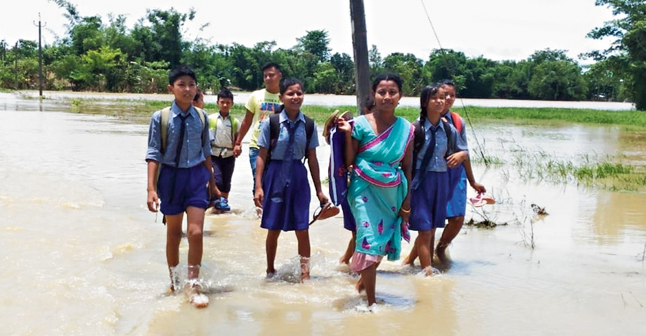 Students navigate a flooded road in Malowkhat in Jorhat.