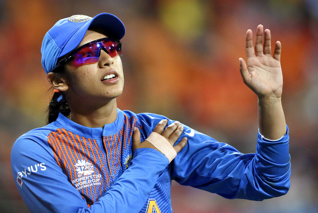 Smriti Mandhana leaves the field clutching her left shoulder after crashing into the signage while fielding against Australia in the Women's T20 Cricket World Cup in Sydney, on Friday