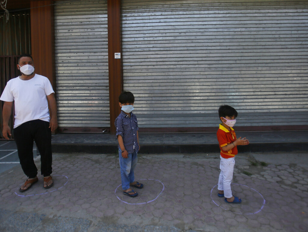 Kashmiri children along with their parent stand in marked circles to maintain social distance as they wait outside a bakery to shop ahead of Eid al-Fitr during a nationwide lockdown to control the spread of coronavirus, in Srinagar, Wednesday, May 20, 2020