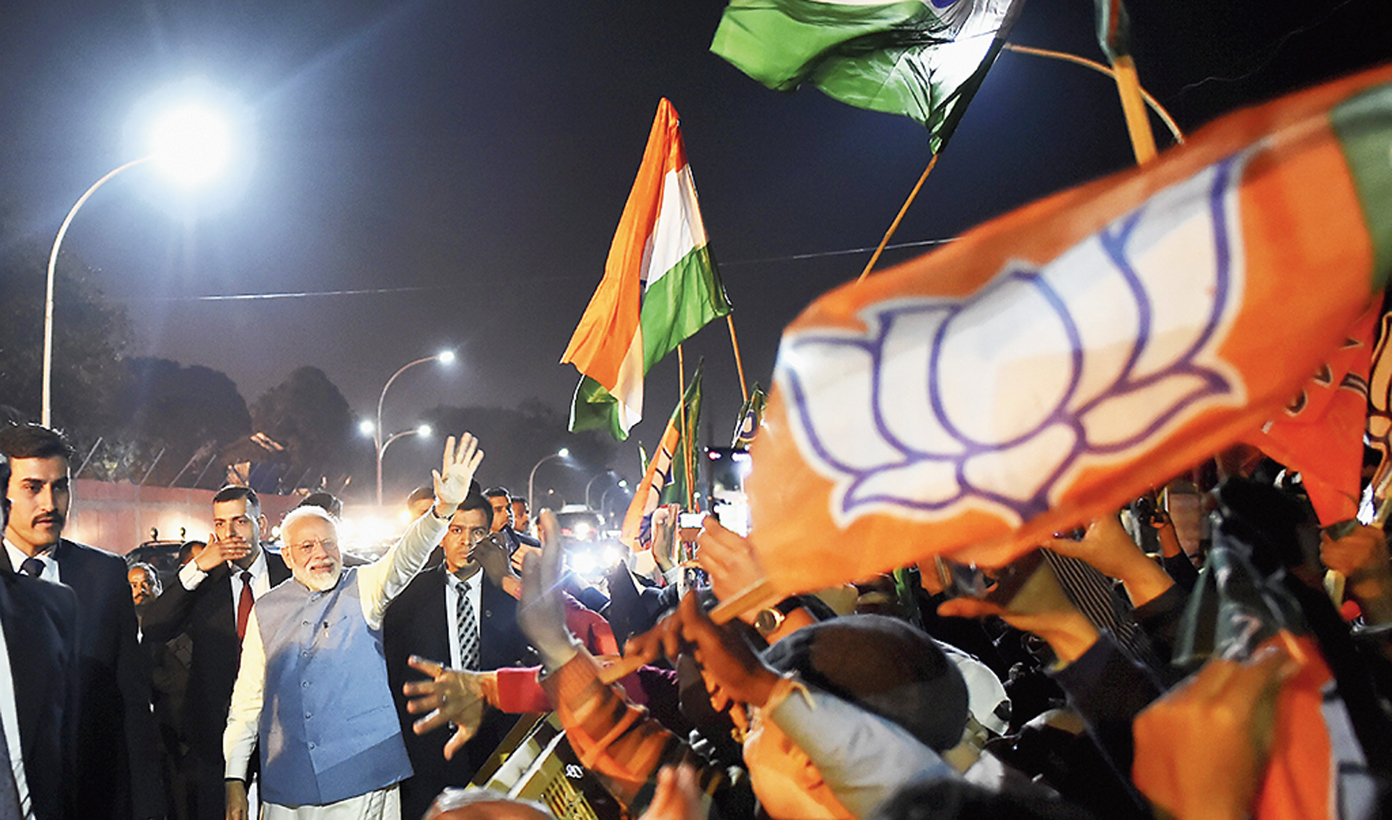 Modi waves at BJP supporters outside the airport in Delhi on Friday.