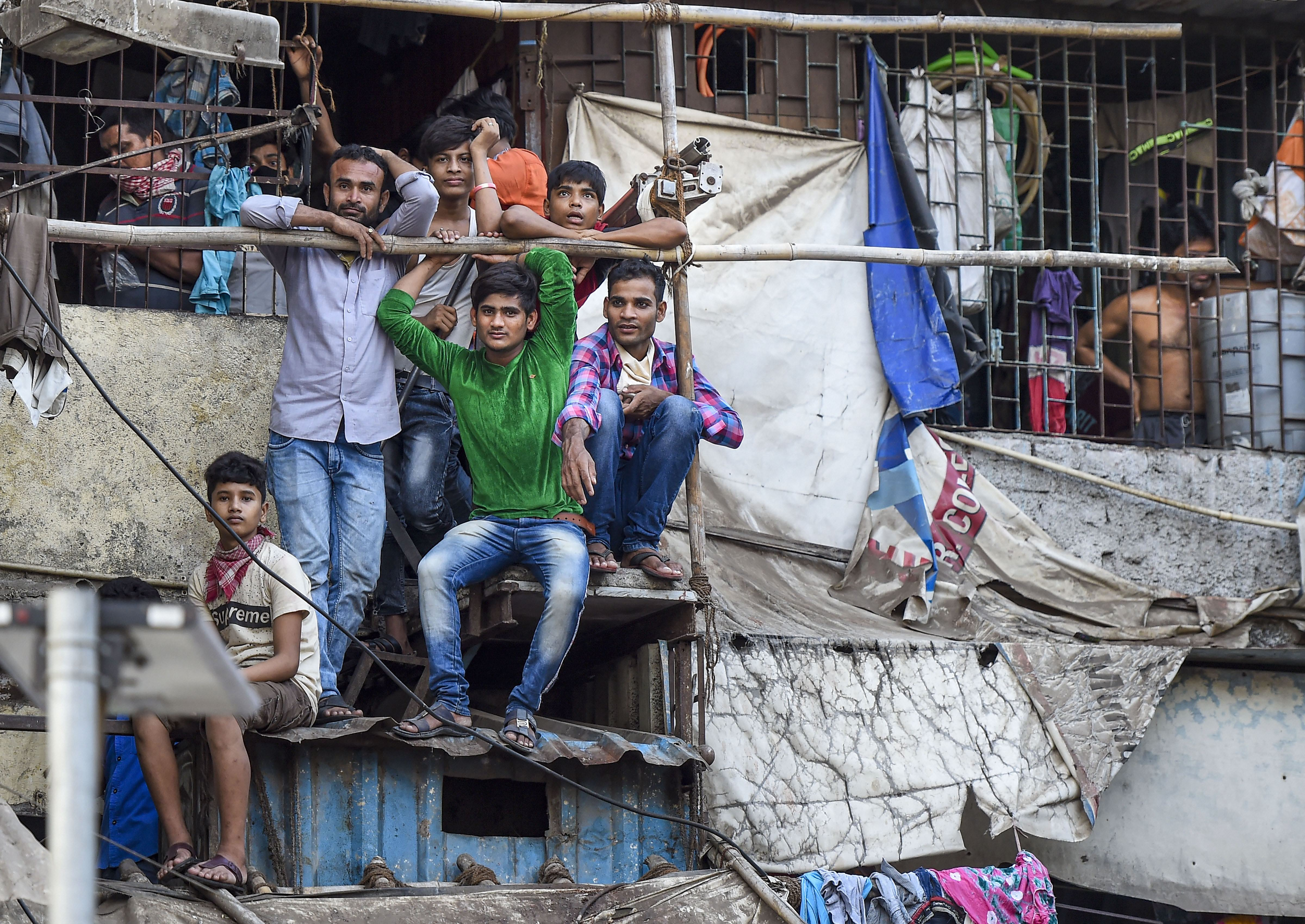 Families of workers look from their houses, after the extension of lockdown till May 3 in the wake of coronavirus pandemic, outside Bandra Railway Station in Mumbai, Tuesday, April 14, 2020.