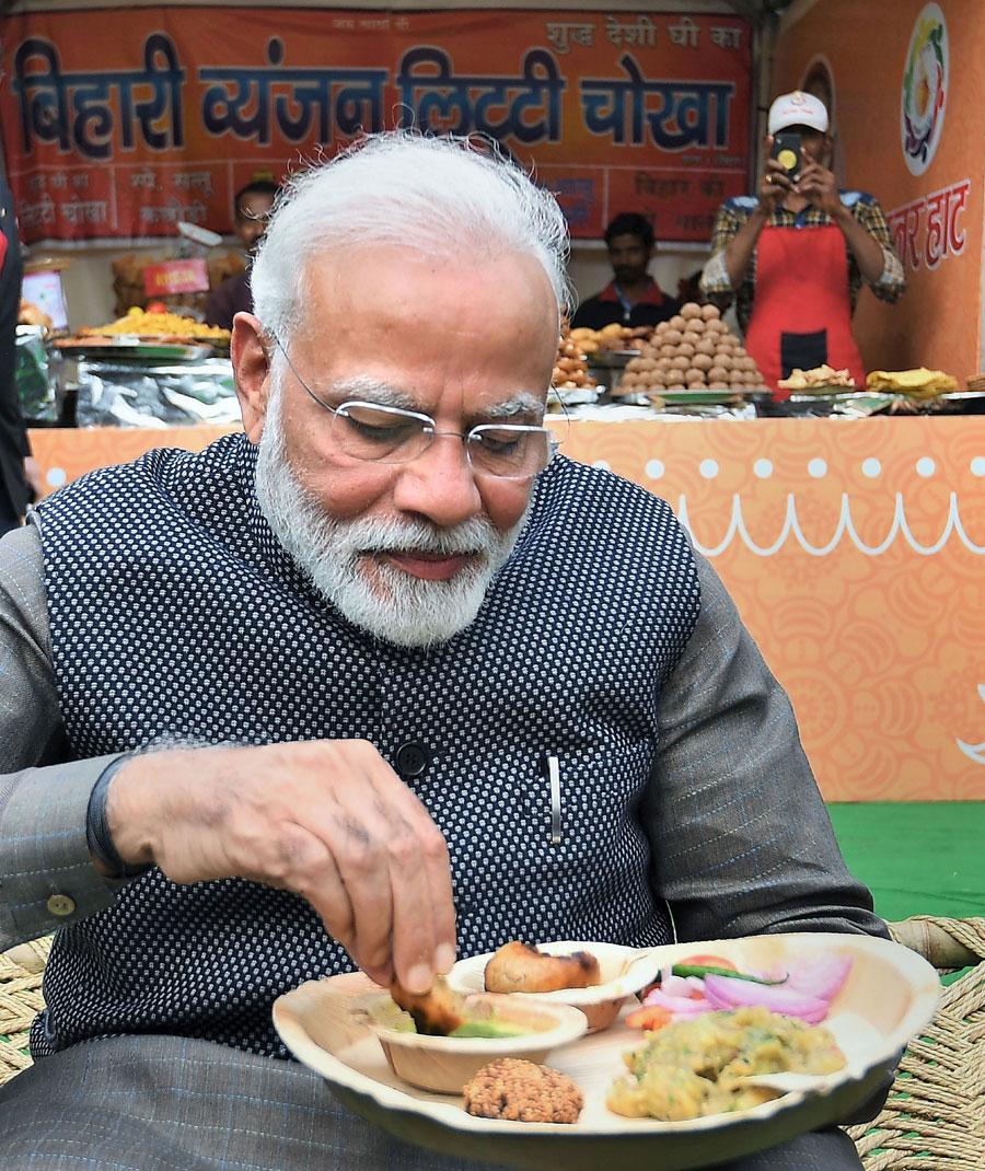 Prime Minister Narendra Modi eats litti-chokha at a snacks stall at Rajpath's Hunar Haat in New Delhi, on Wednesday, February 19, 2020.