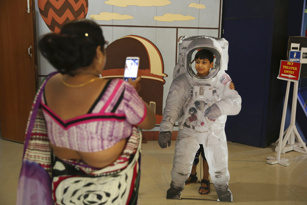 An Indian woman takes a photograph of her son as he poses in a cut-out of an astronaut at the Nehru Planetarium in New Delhi.