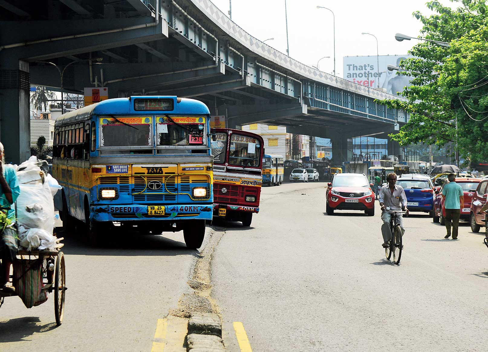 Two airport-bound buses race each other to reach passengers. The divider separating the airport-bound flank of VIP Road and the service lane was demolished so buses can cross over to drop off passengers at the bus stand. The stretch has not been levelled and the main road is a good eight inches higher than the service lane.