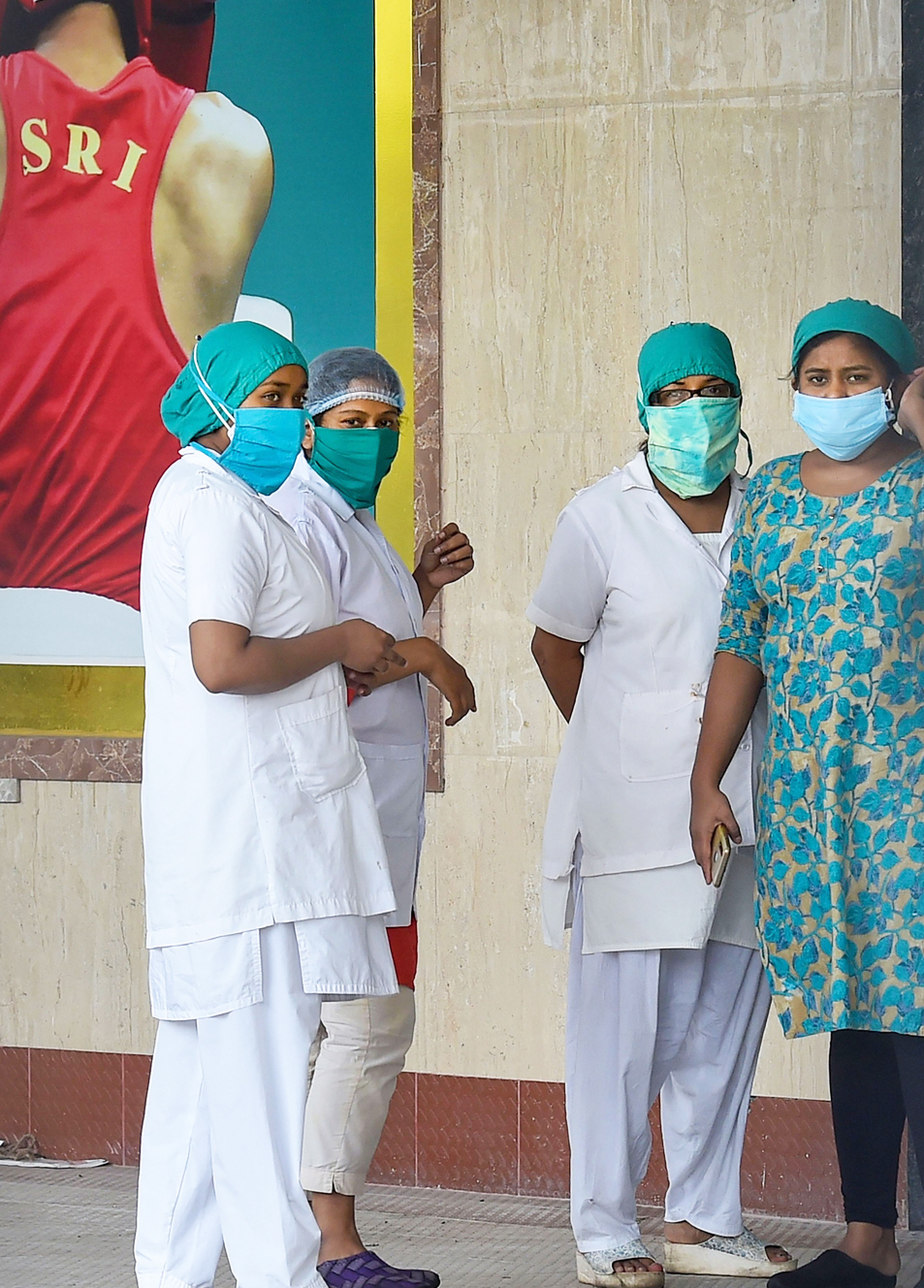 Health workers stand outside a quarantine facility at Dumerjola stadium, during the ongoing Covid-19 nationwide lockdown, in Calcutta, Thursday, June 4, 2020.