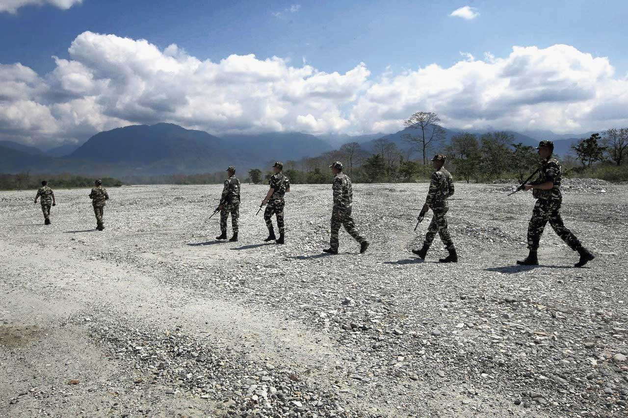 Paramilitary personnel walk through the dry bed of the Pana river at Kalchini near Alipurduar.