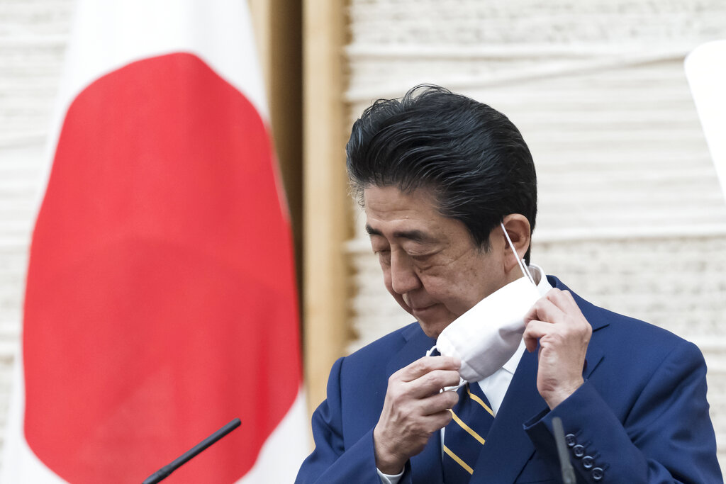 Japan's Prime Minister Shinzo Abe removes his face mask during a press conference at the prime minister's official residence Tuesday, April 7, 2020, in Tokyo. Abe declared a state of emergency for Tokyo and six other prefectures to ramp up defenses against the spread of the coronavirus.