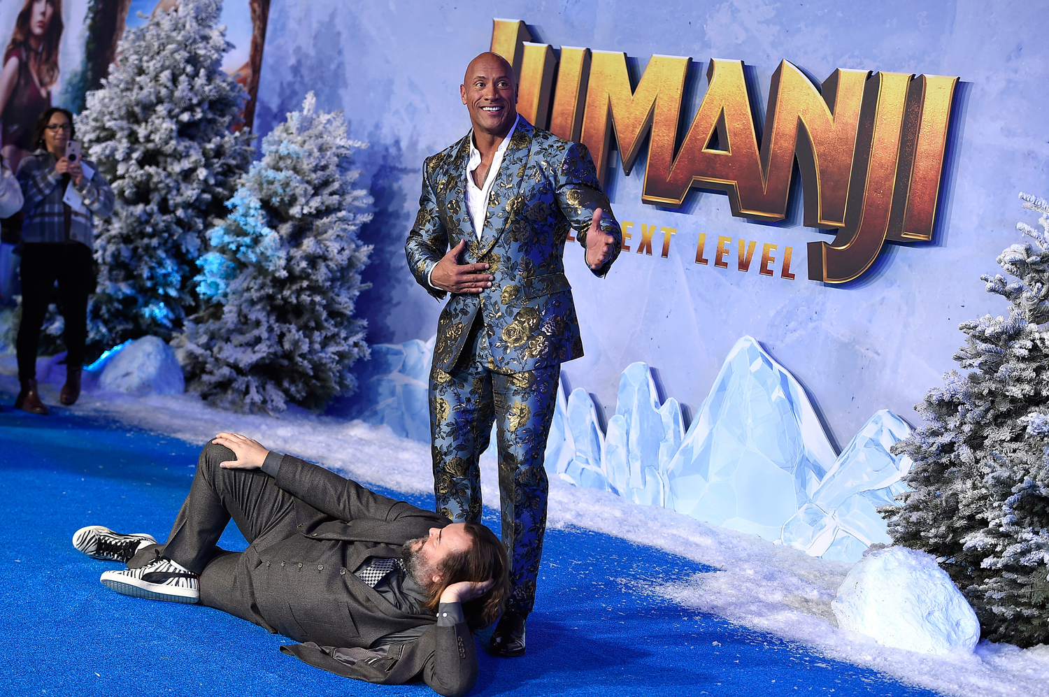 Jack Black, lying down, and Dwayne Johnson pose at the Los Angeles premiere of 'Jumanji: The Next Level' on December 9