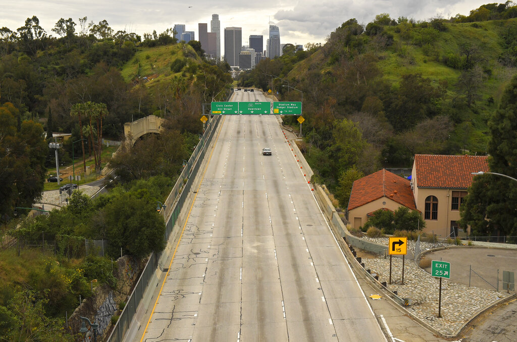 Extremely light traffic moves along the 110 Harbor Freeway toward downtown mid afternoon, Friday, March 20, 2020, in Los Angeles. Traffic would normally be bumper-to-bumper during this time of day on a Friday. California Gov. Gavin Newsom is ordering the state's 40 million residents to stay at home indefinitely. His order restricts non-essential movements to control the spread of the coronavirus that threatens to overwhelm the state's medical system. He called up 500 National Guard troops Thursday to help with distributing food.