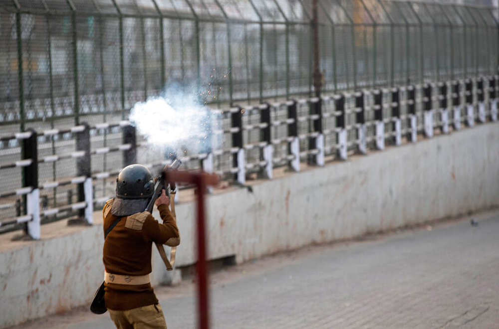 A trooper fires tear gas at protestors during a curfew in Guwahati on December 12