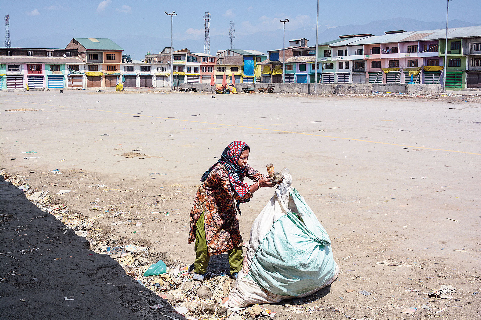 A rag-picker collects bottles at a deserted fruit mandi in Srinagar on Saturday.
