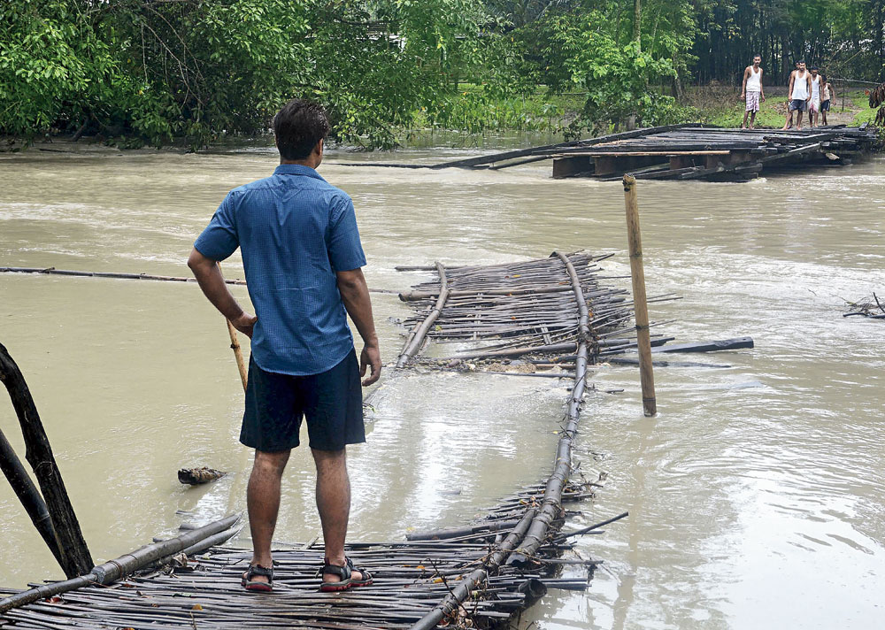 Villagers look at a wooden bridge that washed away in the floods in Nalbari district of Assam on Friday.