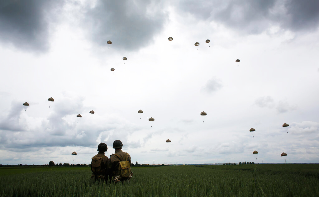 WWII enthusiasts watch French and British parachutists jumping during a commemorative parachute jump over Sannerville, Normandy, on Wednesday, June 5, 2019.