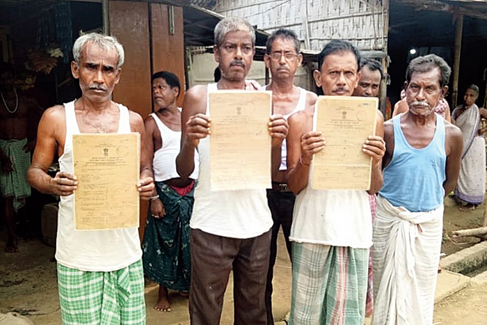 People show their refugee certificates at Choudhurypara