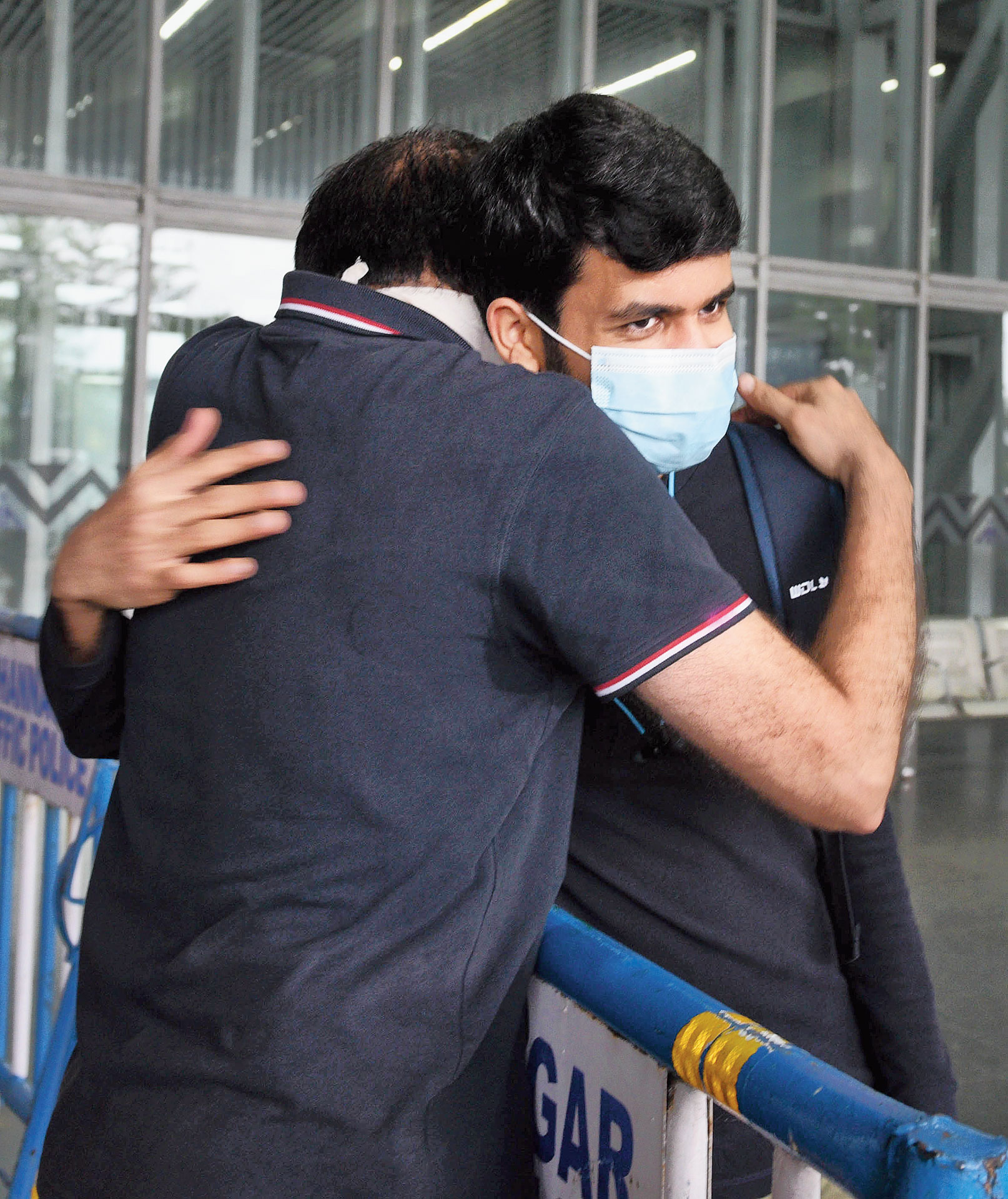 BD Sharma hugs his son Yash as he steps out of the airport's terminal building.