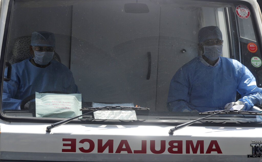 Health workers wearing masks drive an ambulance outside a special ward for possible COVID-19 patients at a hospital in Mumbai, on Tuesday, March 17, 2020