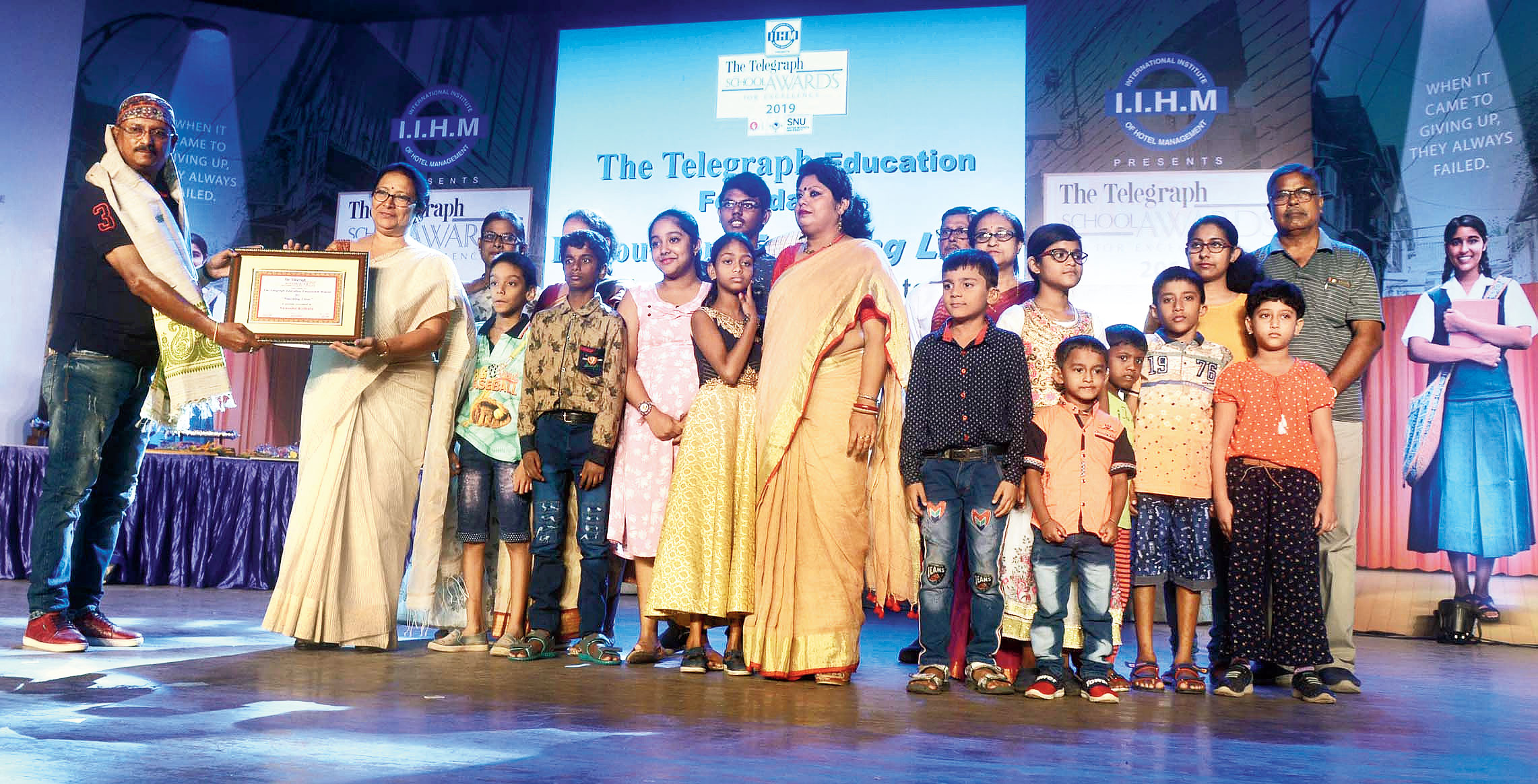 Partha Kar Chowdhury, a pool car driver who collects unsold food from restaurants and distributes them to patients of three government hospitals, hands over The Education Foundation Honour for 'Touching Lives' to teachers and students of Anwesha Kolkata at The Telegraph School Awards for Excellence.
