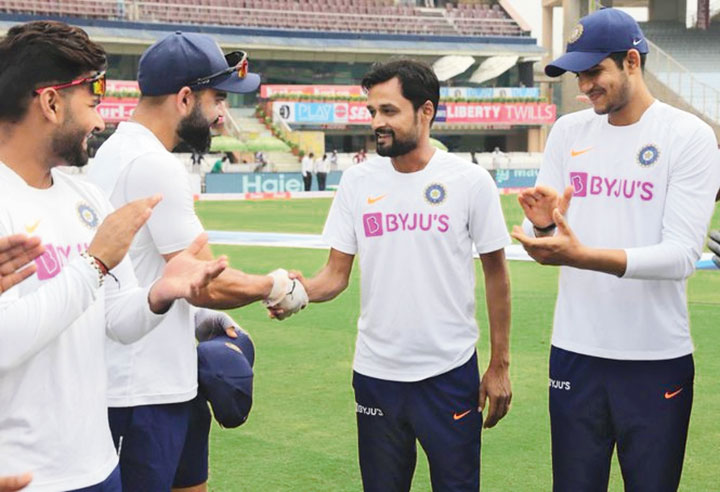 Shahbaz Nadeem gets the Test cap from India captain Virat Kohli as Shubman Gill and Rishabh Pant clap in Ranchi on Saturday