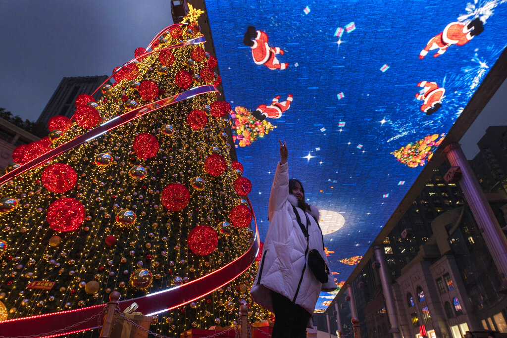 A woman poses for photos near a giant Christmas tree and Christmas themed display during Christmas Eve in Beijing on Tuesday, Dec. 24, 2019.