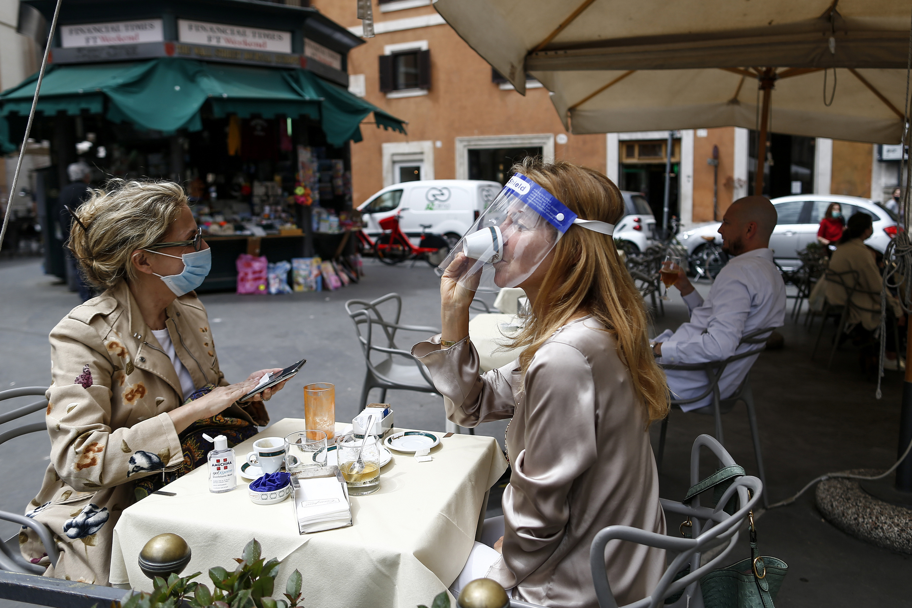 A woman sips coffee under her face shield at a cafe with outdoor tables in Rome