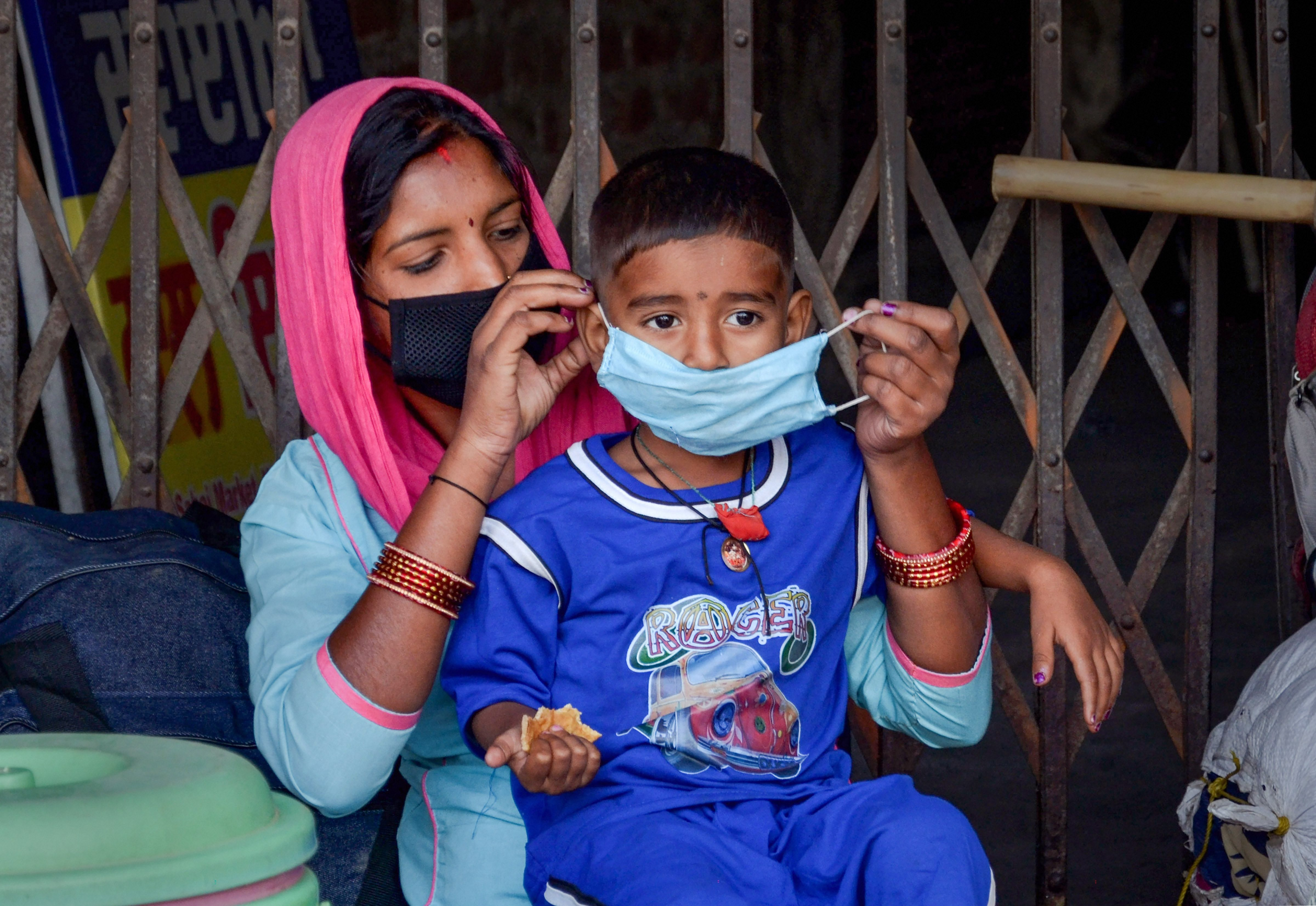 A migrant woman ties a face mask to her son while sitting on the roadside near the railway station seeking arrangements to return to her native place, on the first day of the fifth phase of Covid-19 lockdown, in Amritsar, Monday, June 1, 2020.