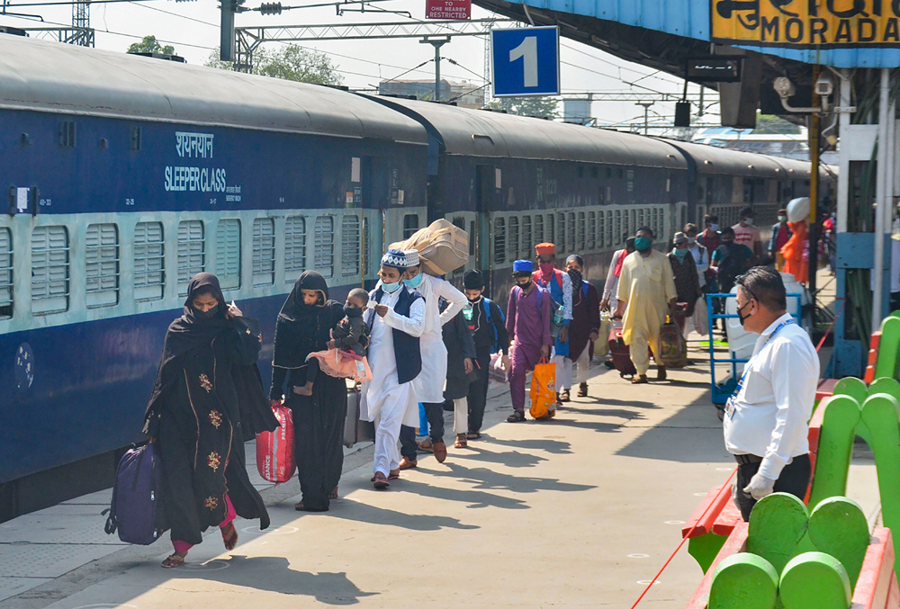 Migrants arrive to board a train to reach their native places in Dhanbad (Jharkhand) and Bihar at a railway station, during the ongoing Covid-19 lockdown, in Moradabad, Sunday, May 31, 2020.