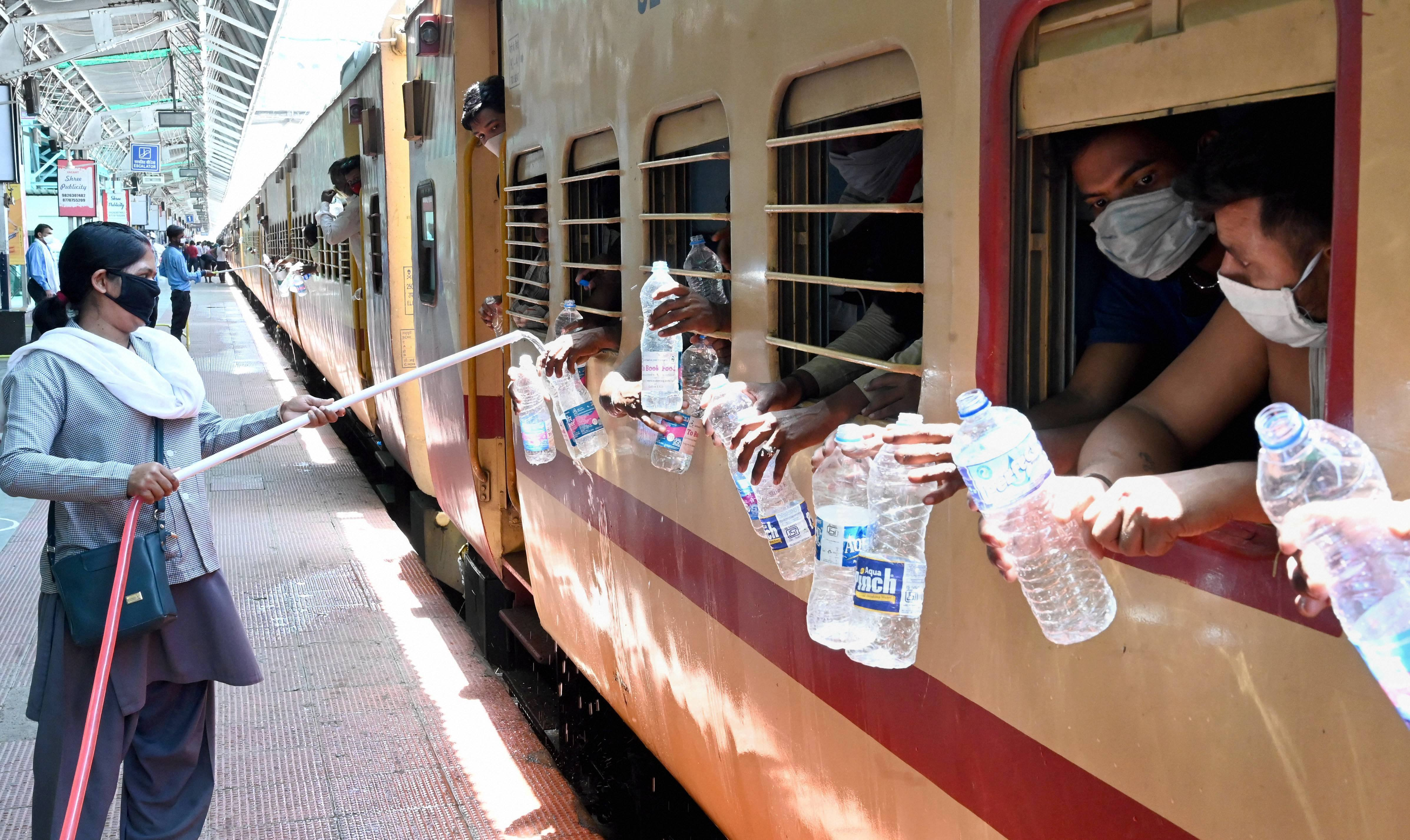 A railway employee refills water bottles of migrants sitting in a train to reach their native places, during the ongoing Covid-19 lockdown, in Jabalpur, Saturday, May 23, 2020.