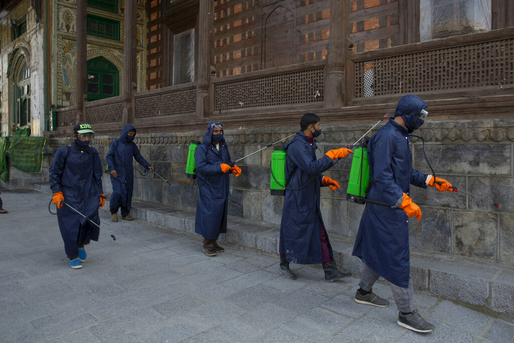 Srinagar Municipal Corporation staff spray disinfectants as a precautionary measure against COVID-19 outside the shrine of Shah-e-Hamadan in Srinagar, Kashmir