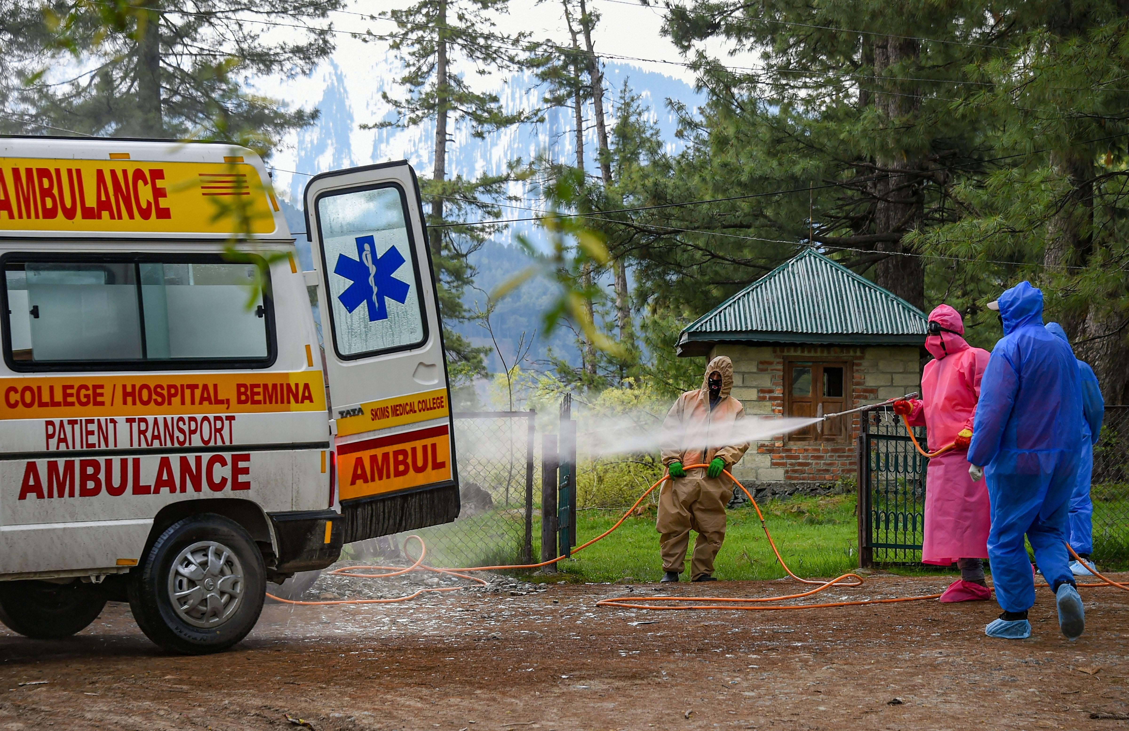 Health officials spray disinfectant on an ambulance