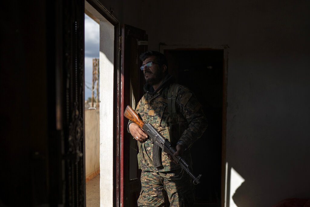 In this February 17, 2019 file photo, Dia Hassakeh, 45, a fighter in the Kurdish-led US-backed Syrian Democratic Forces, looks out of a building in Baghouz.