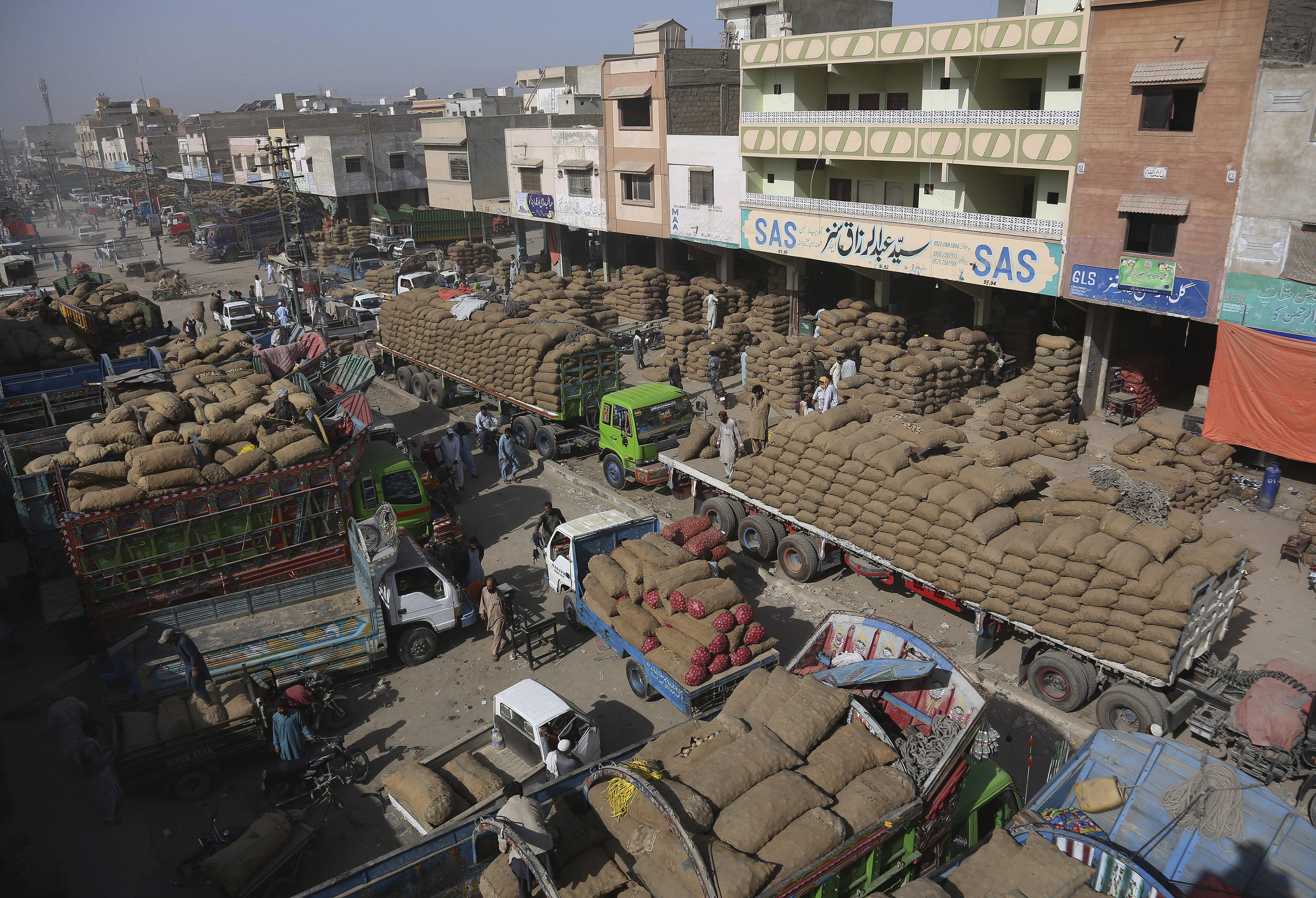 Laborers unload onions and potato from truck at a wholesale fruit and vegetable market in Karachi, Pakistan