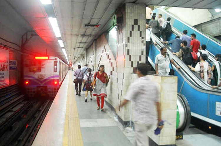 A Calcutta Metro train leaves the platform of a station.