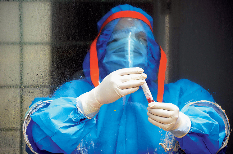 A health worker with a freshly collected blood sample at Guru Nanak School in Ranchi