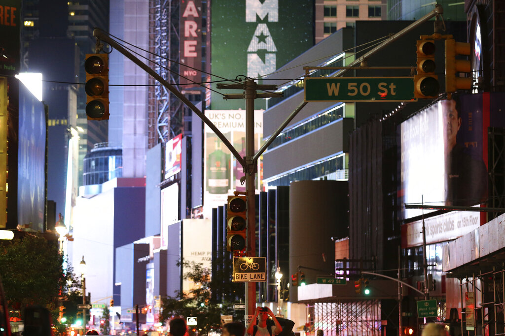 Traffic lights hang without power in Times Square during a power outage, on Saturday, July 13, 2019, in New York.